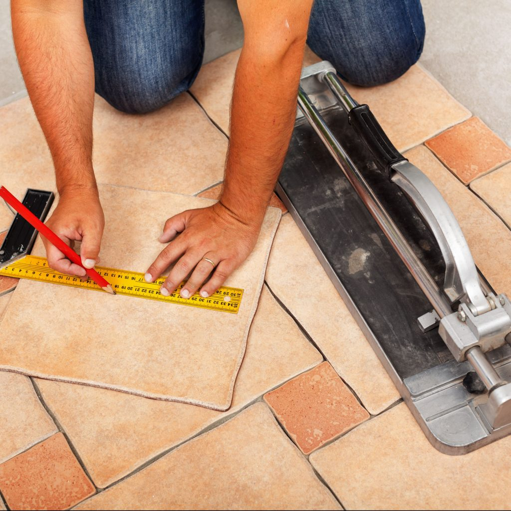 Man Measuring and Cutting Tile for Installation