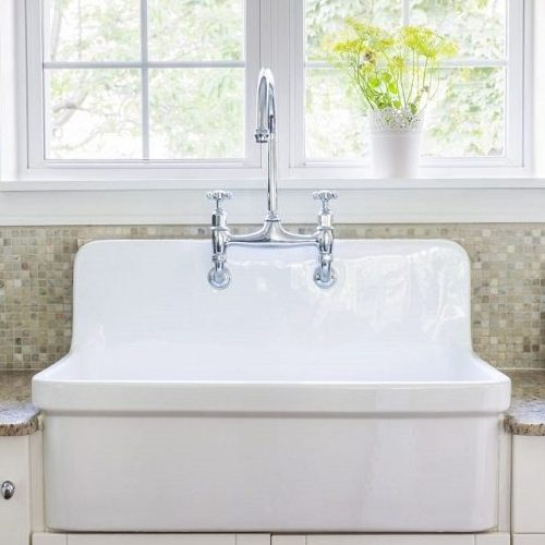 A Picture of a Kitchen Interior with a Large Rustic White Porcelain Sink.