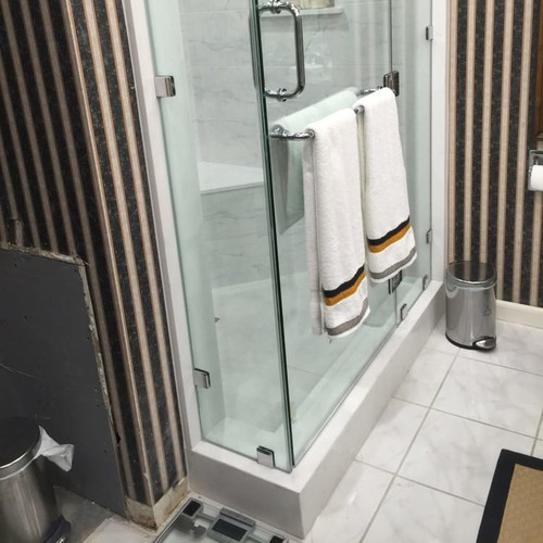 A Picture of a Shower with Towels Hanging On the Door.