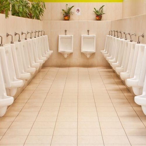 A Picture of White Porcelain Urinals in a Public Bathroom.